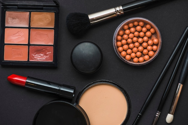 Various makeup products on black background