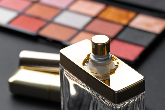 Various makeup products on black texture background. close up