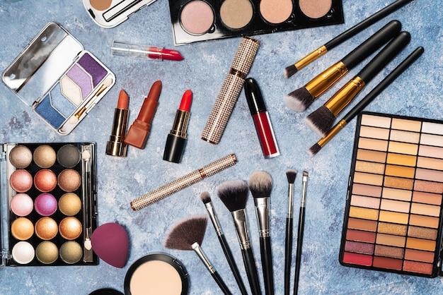 Различные продукты для макияжа, кисти на синем фоне