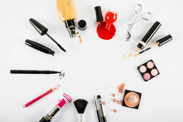 Various makeup products forming circular frame on white background