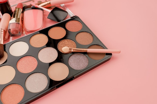 Various makeup products on pink background with copyspace