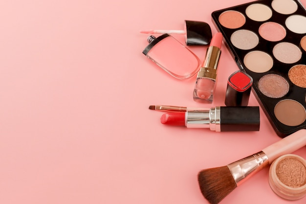 Various makeup products on pink copyspace
