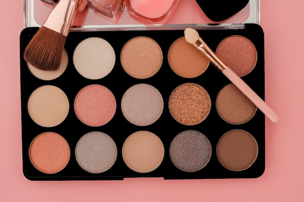 Various makeup products on pink surface with copyspace