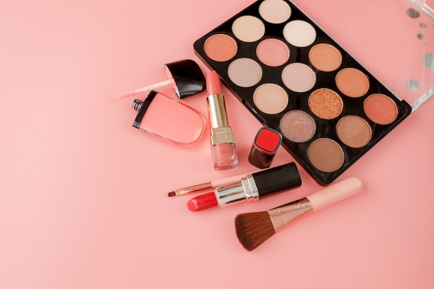 Various makeup products on pink