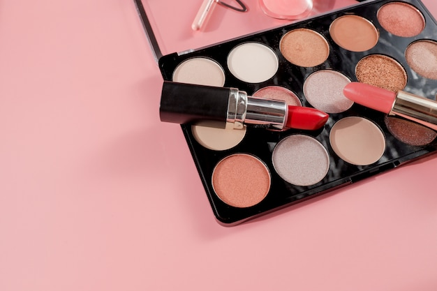 Various makeup productson pink background with copyspace
