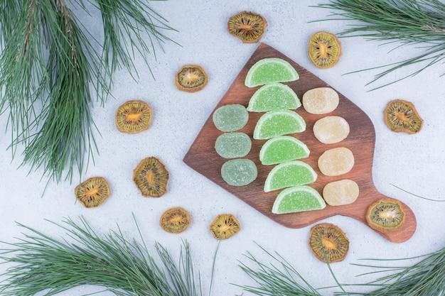 Различные мармелады на деревянной доске с сушеными дольками киви.