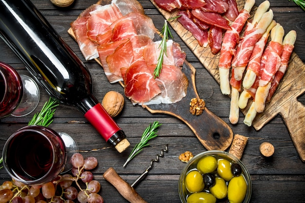 Various meat appetizer with olives, jamon and red wine.