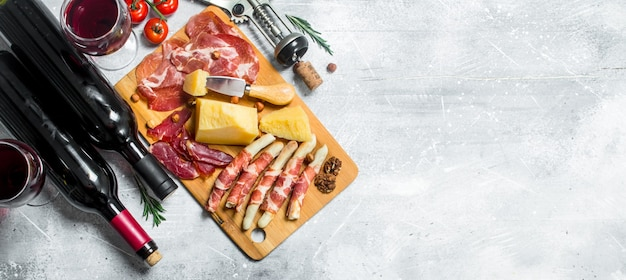 Various meat and cheese snacks with red wine on rustic table.