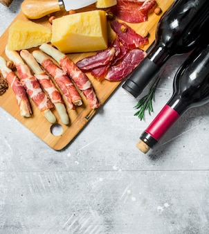 Various meat and cheese snacks with red wine on wooden table.
