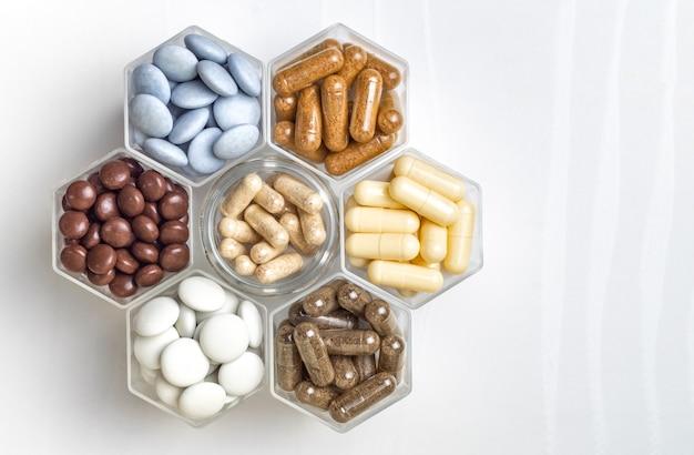 Различные медицинские капсулы и таблетки в гексагональных банках в виде сот.