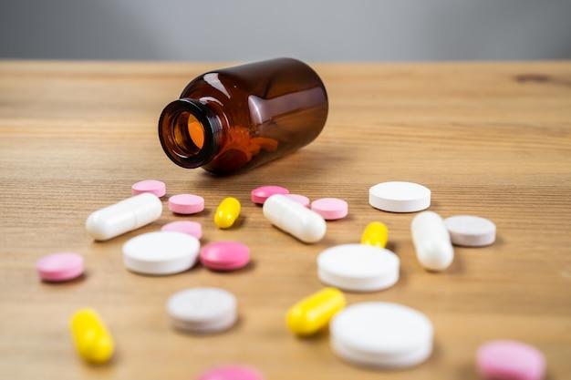Различные лекарства и витамины, пузырек с таблетками. деревянный фон, место для вставки текста. здоровье и аптека.