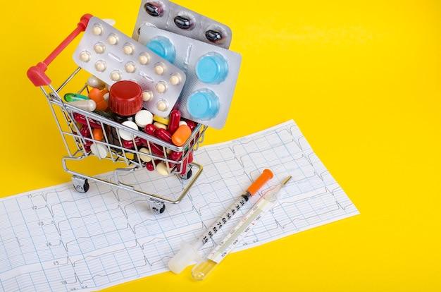 Различные лекарства в тележке на желтой поверхности
