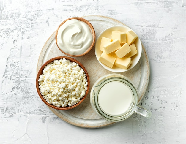 Various milk products on white wooden cutting board, top view