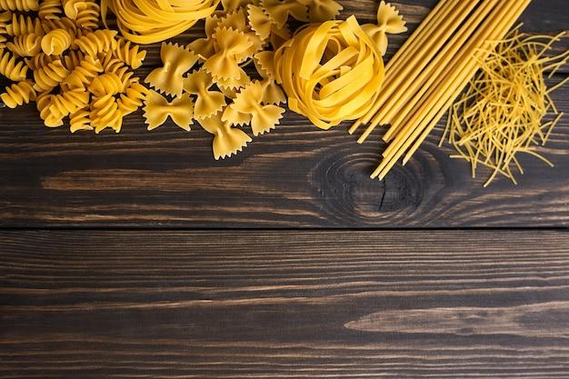 暗い木製のテーブルにパスタのさまざまなミックス。イタリア料理