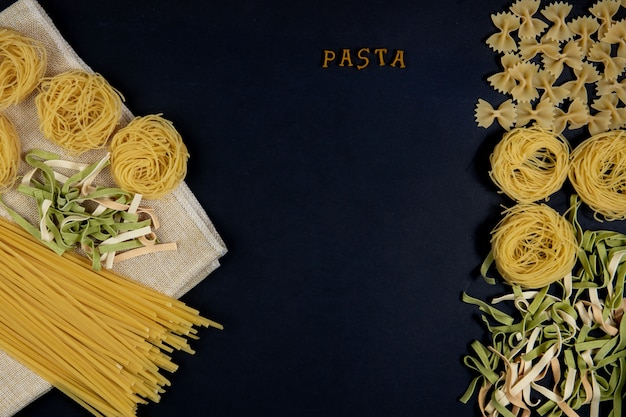 Various mix of pasta on dark background, metal spoons. food concept. the word pasta italian food and menu concept.
