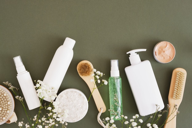 Various mock up blank bottles and jars for cosmetics on dark green background, wooden brushes for body care and massage