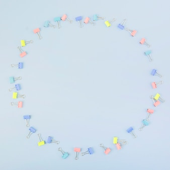 Various multi colored bulldog clips forming circle on blue backdrop