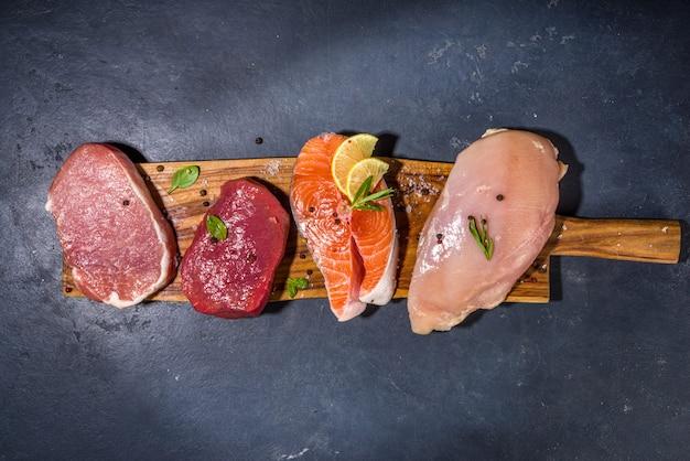 다양한 자연 식품, 높은 동물성 단백질 공급원 - 돼지고기, 쇠고기 고기 스테이크, 닭 가슴살 필레, 계란, 흰색 탁자 위에 있는 연어 생선 상위 뷰 복사 공간
