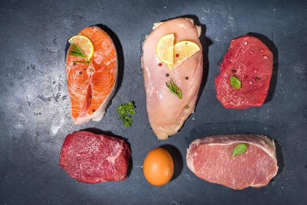 Различная натуральная пища, источники с высоким содержанием животного белка - свинина, стейки из говядины, филе куриной грудки, яйца, лосось на фоне белого стола, вид сверху, копия пространства