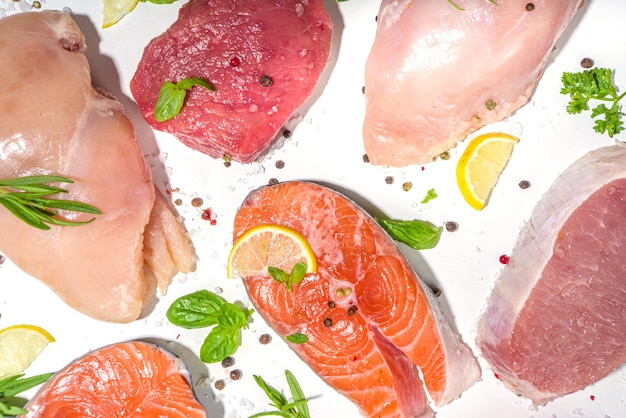 Various natural food, high animal protein sources - pork, beef meat steaks, chicken breast fillet, eggs, salmon fish on white table background top view copy space