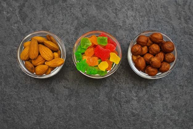 黒い大理石の背景にさまざまなナッツや砂糖漬けの果物