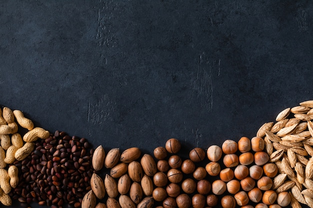 Various nuts on black stone table