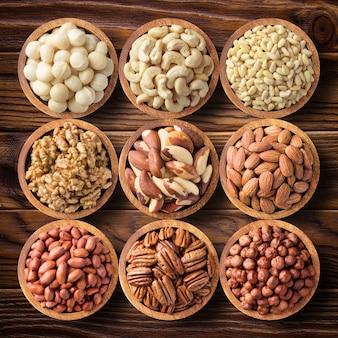 Различные орехи в деревянных мисках, вид сверху. пищевой фон: пекан, фундук, грецкий орех, миндаль, макадамия, кешью, арахис, бразилия, сосна