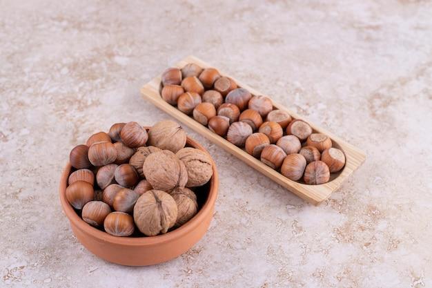 大理石の表面の木製のボウルにさまざまなナッツ