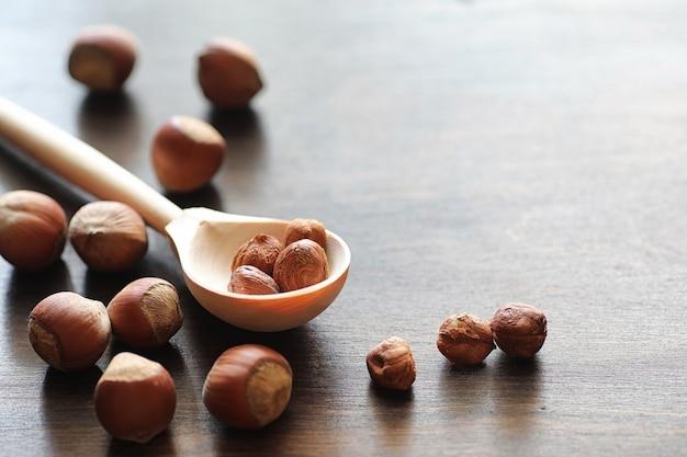 Различные орехи разбросаны и в ложке на деревянном столе текстуры
