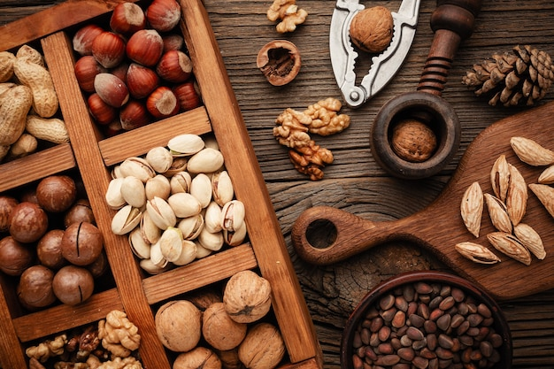 Various nuts selection: peanuts, hazelnuts, chestnuts, walnuts, pistachio and pecans in wooden box.