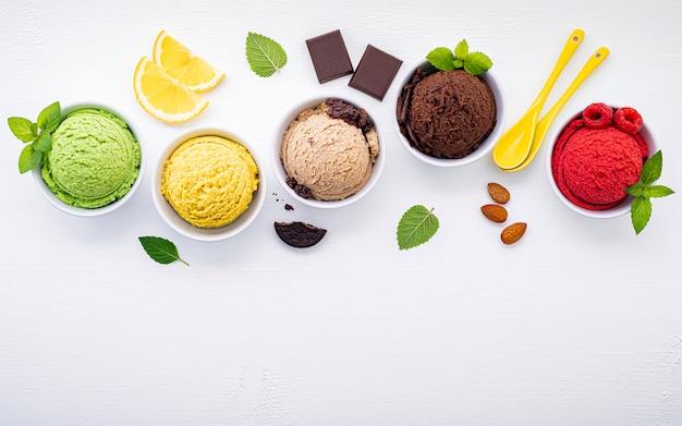 Различный шарика вкуса мороженого настроил на белой деревянной предпосылке.