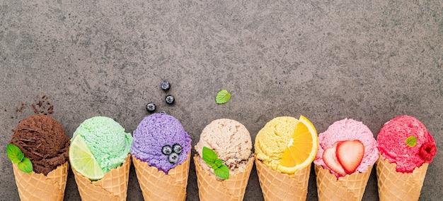 어두운 돌 배경에 설정된 콘의 다양한 아이스크림 맛.