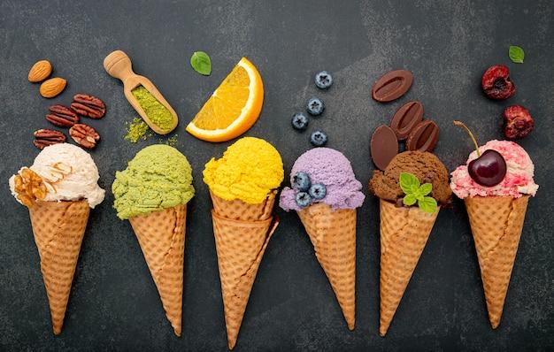어두운 돌 배경에 콘 설치에 다양한 아이스크림 맛.