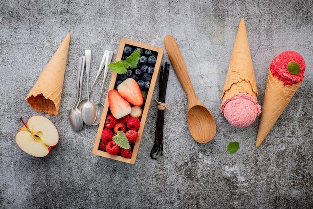 コンクリートの背景に木製の箱のセットアップでベリーとコーンのさまざまなアイスクリームの味