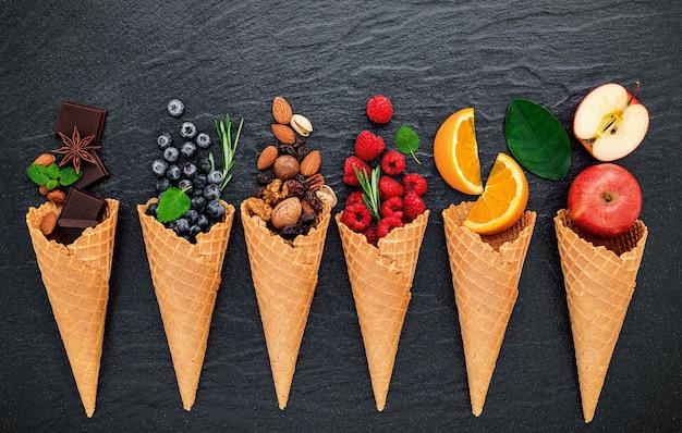 어두운 돌 배경에 설정된 콘에 아이스크림 맛에 대한 다양한 성분.
