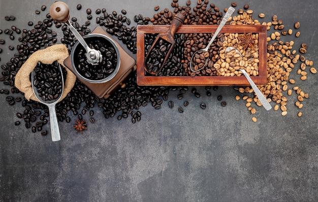 Различные обжаренные кофейные зерна в деревянной коробке с ручной настройкой кофемолки на темном камне.