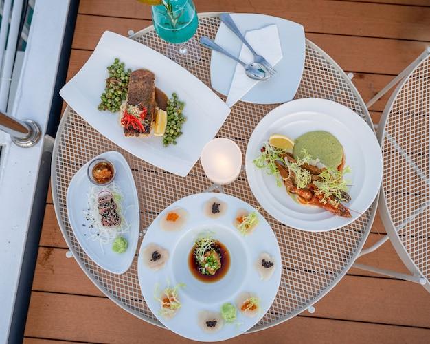 Различные морепродукты с лососем, креветками, моллюсками, тунцом в белой тарелке с синим коктейлем на столе во внутреннем дворике