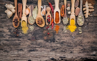 Various of spices and herbs in wooden spoons on shabby wooden.