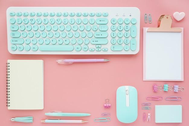 ピンクの背景にさまざまな事務用品や事務用品がきれいにレイアウトされています。テキストのためのスペース。フラットなレイアウト、トップビュー。