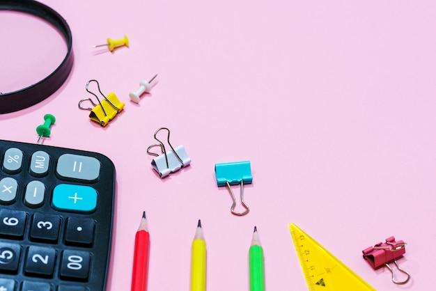 ピンクの背景にさまざまな事務用品が学校のコンセプト計算機と拡大鏡に戻って...