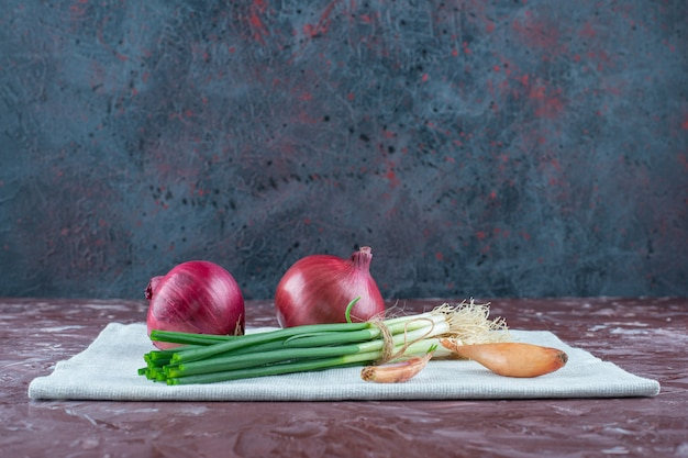Различные луковицы на полотенце на мраморной поверхности