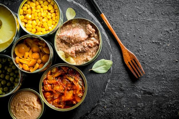 포크로 돌 보드에 통조림 식품의 다양한 오픈 깡통. 검은 소박한 배경에