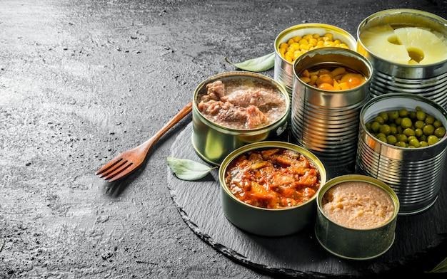素朴なテーブルの上のフォークと石のボード上の缶詰食品のさまざまなオープンブリキ缶