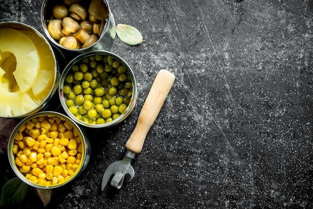 素朴なテーブルの缶詰のさまざまなオープンブリキ缶