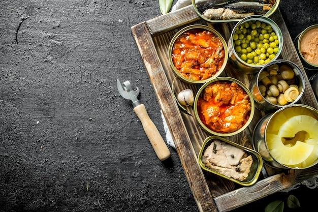 쟁반에 통조림 식품의 다양한 오픈 깡통. 검은 소박한 배경에