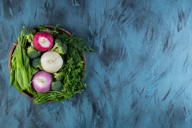Various organic radishes and green leaves on blue background.