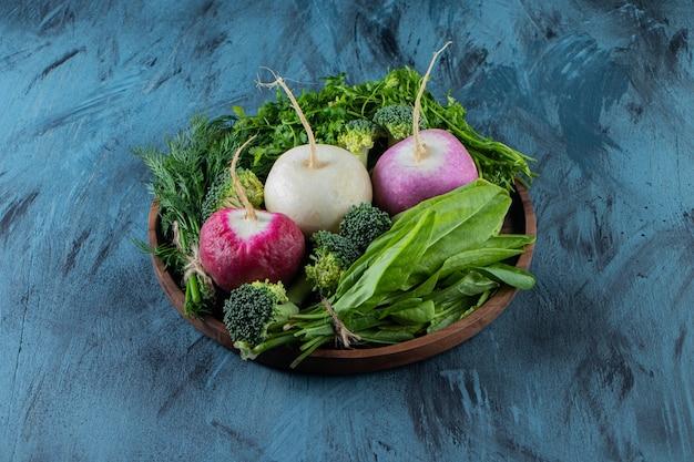 Vari ravanelli organici e foglie verdi sulla superficie blu.