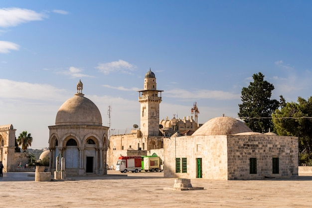 Various outbuildings, walls and minarets in the stone paved courtyard surrounding the dome of the rock islamic shrine in jerusalem israel.