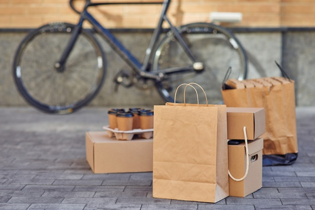 Various packages with food pizza boxes and four coffee cups standing on the street road