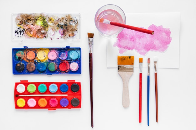 Various paint brushes and palette in box